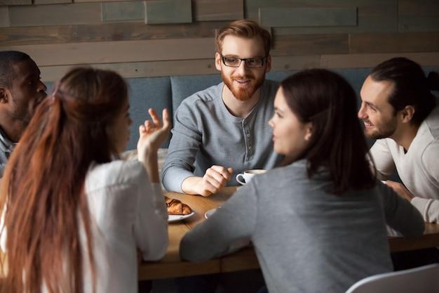 Różnorodni młodzi ludzie opowiada zabawę w kawiarni i ma wpólnie