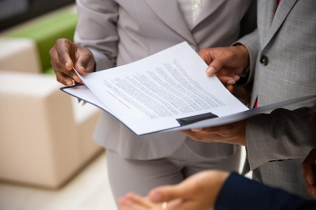 Różnorodni partnerzy biznesowi czytający umowę razem