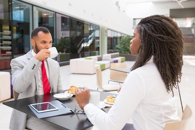 Różnorodni partnerzy biznesowi jedzący śniadanie w lobby biurowym