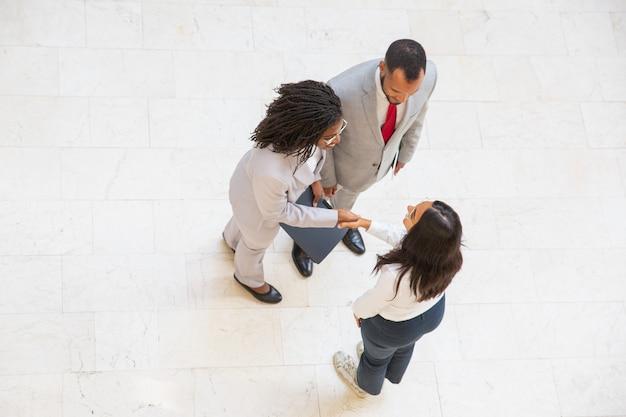 Różnorodni partnerzy biznesowi witają się w korytarzu biurowym