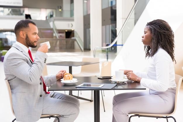 Różnorodni partnerzy lub koledzy spotykający się przy filiżance kawy