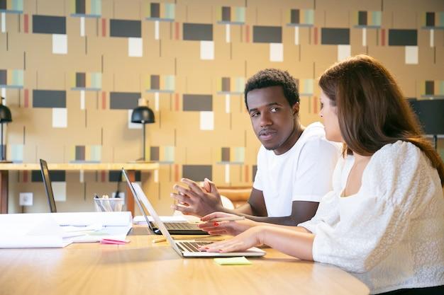 Różnorodni projektanci siedzą przy stole z laptopami i planami, rozmawiając i omawiając projekt