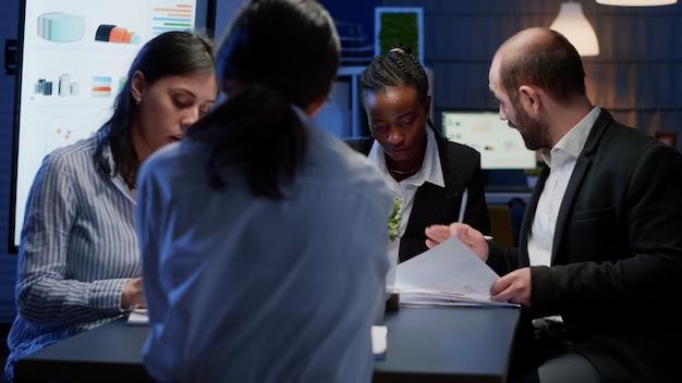 Różnorodni przedsiębiorcy biznesowi siedzą przy stole konferencyjnym i pracują nad rozwiązaniem do zarządzania