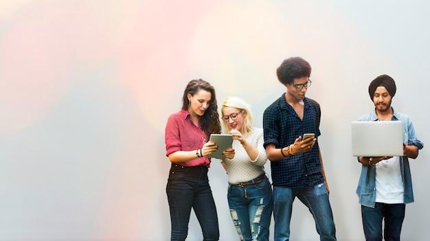 Różnorodni przyjaciele korzystający z urządzeń cyfrowych