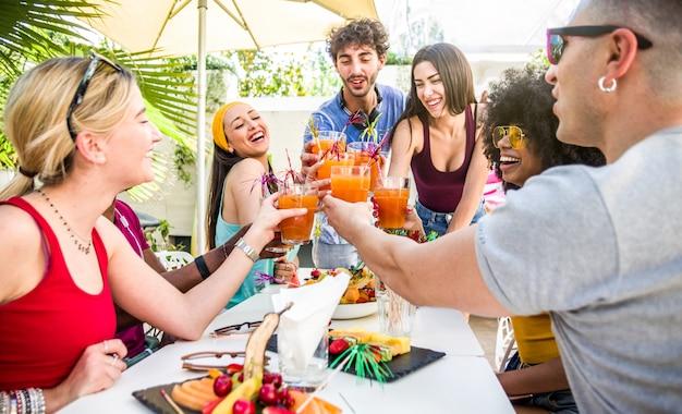 Różnorodni przyjaciele ludzi wychodzą na tosty i piją koktajle na świeżym powietrzu