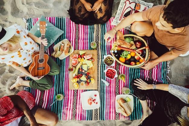 Różnorodni przyjaciele na pikniku na plaży