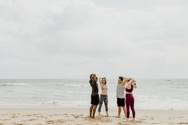 Różnorodni przyjaciele rozciągający się na plaży
