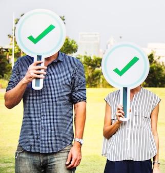 Różnorodni przyjaciele trzyma checkmark ikony