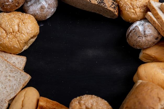 Różnorodni rodzaje chleba umieszczający na czarnym drewnianym tle