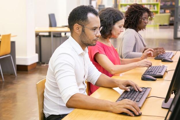Różnorodni stażyści przystępujący do testów online w klasie komputerowej