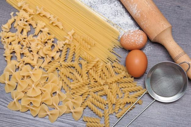 Różnorodni typ lub surowy makaron na drewnianym tle i składniki dla makaronów jajek, mąka.