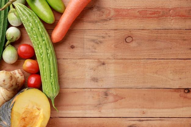 Różnorodni warzywa na drewnianym tle. widok z góry