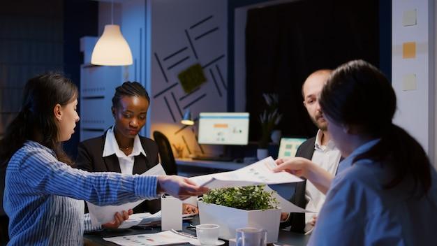 Różnorodni, wieloetniczni biznesmeni dzielą się wykresami zarządzania, przepracowują papierkową robotę na spotkaniu biurowym...