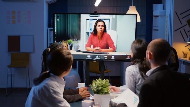 Różnorodni, wieloetniczni biznesmeni omawiają strategię zarządzania podczas wideorozmów online