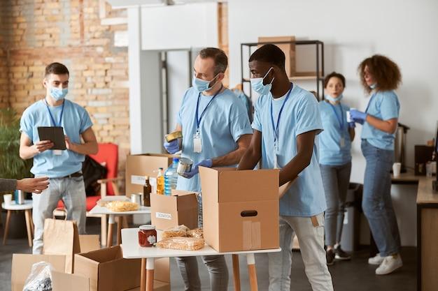 Różnorodni wolontariusze w niebieskich mundurach ochronnych maskach i rękawiczkach rozdzielają darowizny razem