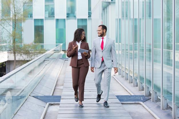 Różnorodni współpracownicy idący miejską ścieżką