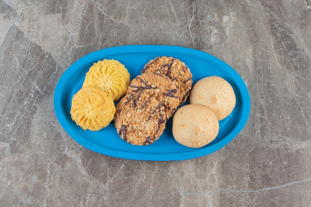 Różnorodnie ciasteczka na drewnianym talerzu na marmurze.
