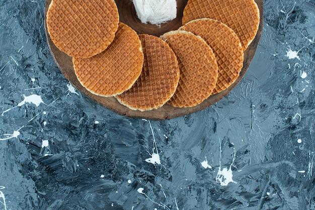 Różnorodnie deser na desce, na niebieskim stole.