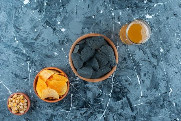 Różnorodnie przystawki w miskach i szklanka piwa na niebieskim stole.