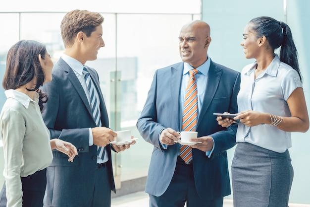 Różnorodność azjatycki zespół biznes z kawą przed biurem