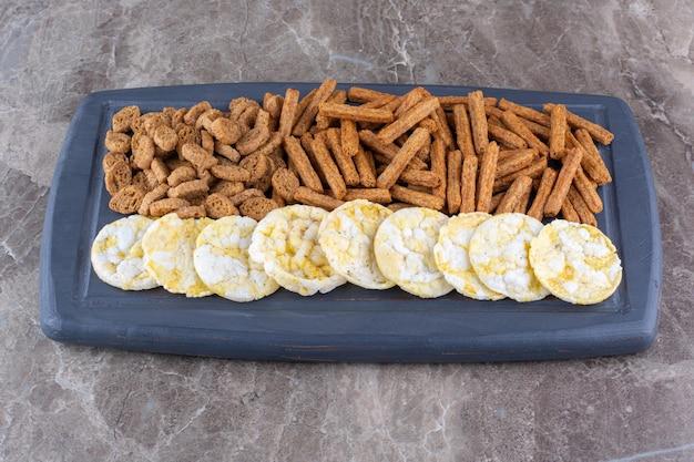 Różnorodność chrupiących krakersów na ciemnym talerzu. zdjęcie wysokiej jakości