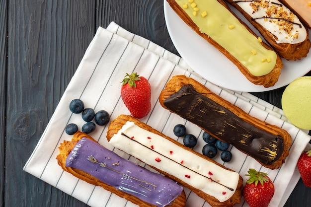 Różnorodność ciast eclair na serwetce kuchennej na drewnianym stole
