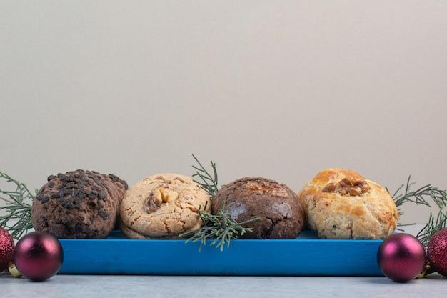 Różnorodność ciasteczek na niebieskim talerzu z bombkami. zdjęcie wysokiej jakości