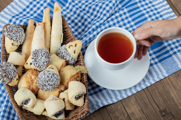 Różnorodność ciastek na talerzu z filiżanką herbaty na bok.