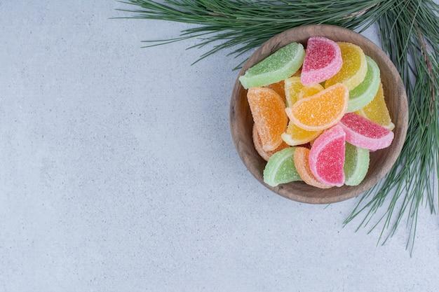 Różnorodność cukierków marmoladowych w drewnianej misce.