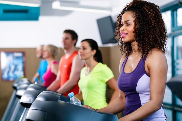 Różnorodność grupy młodych i starszych ludzi na bieżni w siłowni