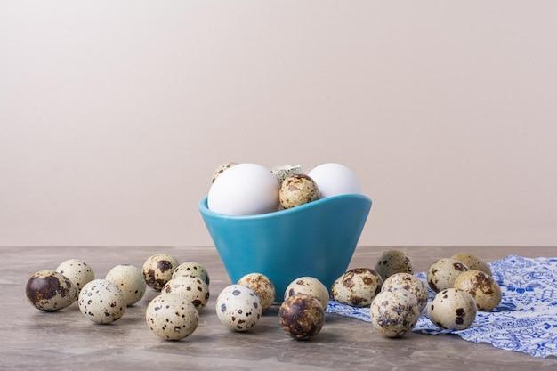 Różnorodność jajek w niebieskiej filiżance i na ziemi.