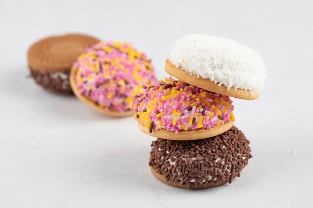 Różnorodność kremowych ciasteczek francuskich z posypką na białej powierzchni.