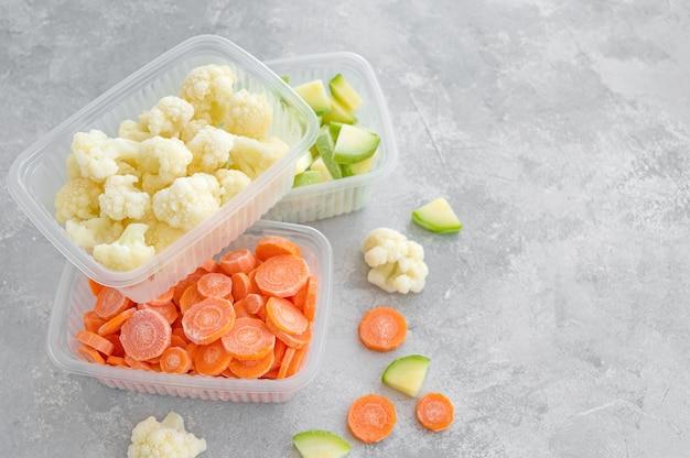 Różnorodność mrożonych warzyw w plastikowych pojemnikach na szarym betonowym tle. zdrowe jedzenie. skopiuj miejsce.