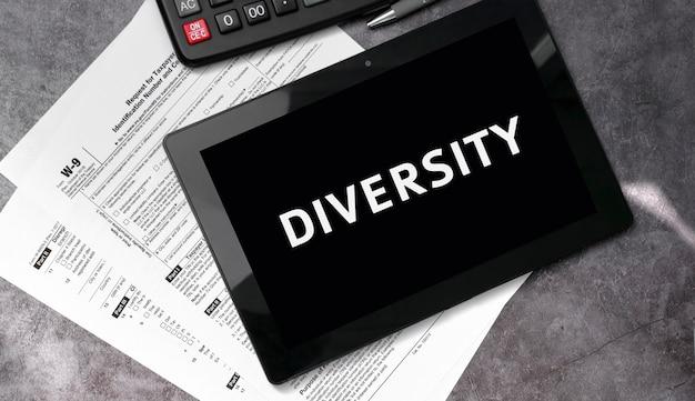 Różnorodność na czarnym tablecie, z formularzami podatkowymi i kalkulatorem