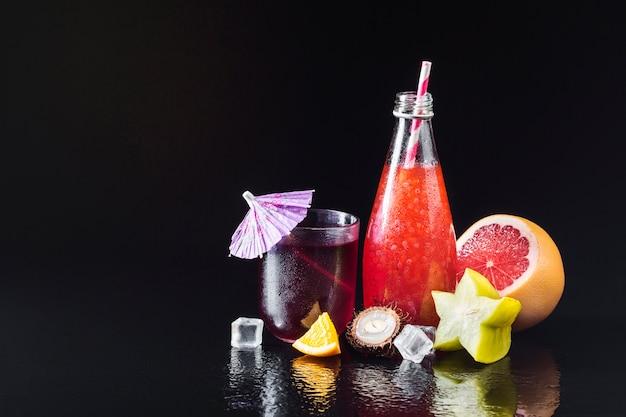 Różnorodność owoców i soków na czarnym tle