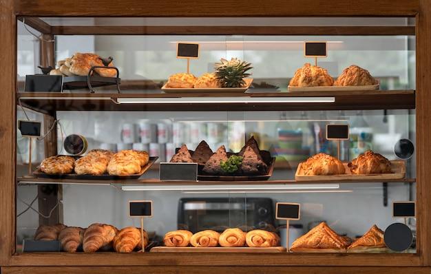 Różnorodność pieczonego chleba i deseru w szklanej gablocie w sklepie piekarniczym