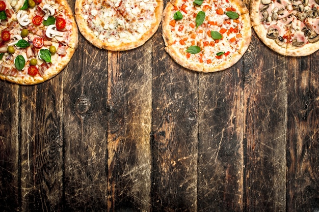 Różnorodność pizzy. na drewnianym tle