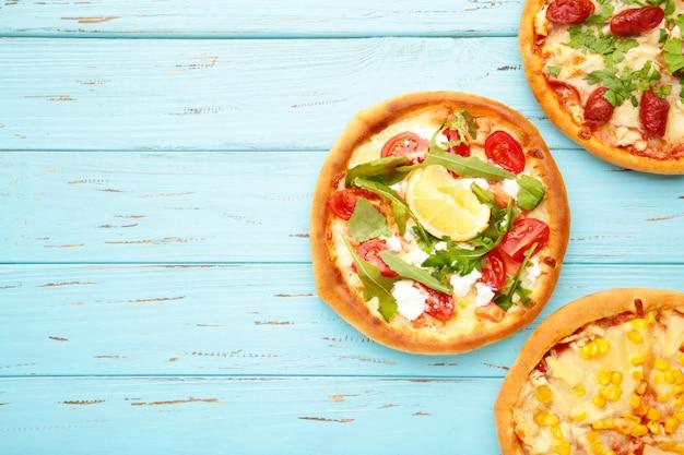 Różnorodność pizzy na niebieskim drewnianym stole