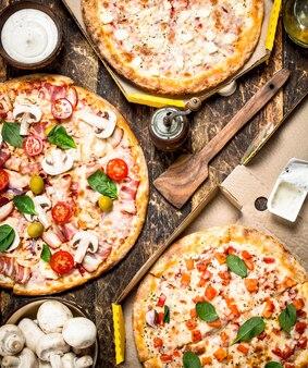 Różnorodność pizzy z grzybami i sosem na drewnianym stole