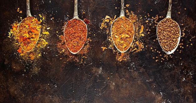 Różnorodność przypraw i ziół na ciemnym stole. gotowanie w tle. widok z góry. składniki do gotowania. menu tła tabeli. skopiuj miejsce.