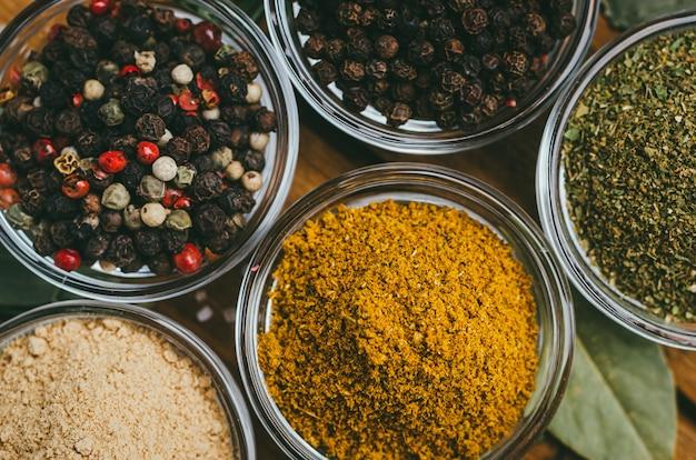 Różnorodność przypraw w okrągłych szklanych misach. mielony imbir, chmiel-suneli, kari, czarny pieprz i mieszanka.