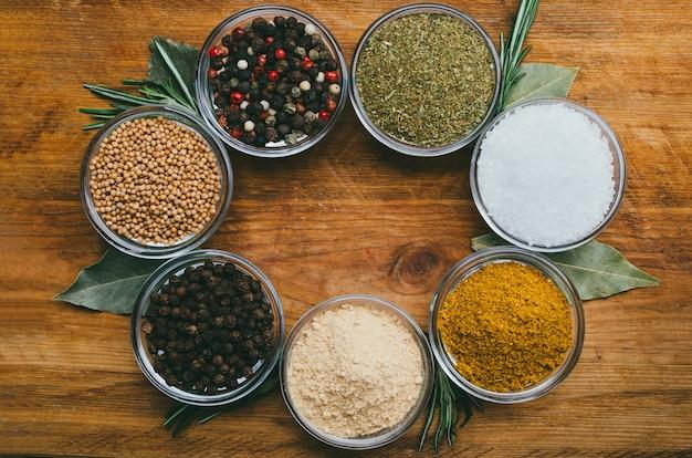 Różnorodność przypraw w okrągłych szklanych misach. mielony imbir, chmiel suneli, kari, czarny pieprz i mix
