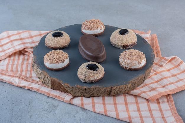 Różnorodność pysznych słodkich herbatników z truflami na kawałku drewna.