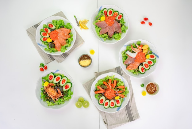 Różnorodność sałat z łososiem, maguro, pająkiem, kani i owocami morza na stole