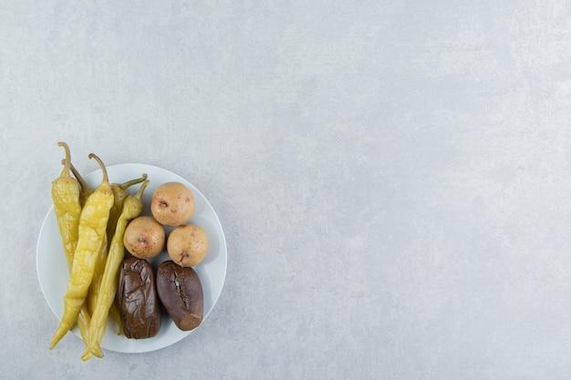 Różnorodność sfermentowanych warzyw i owoców na białym talerzu.