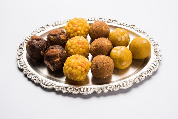 Różnorodność słodkiego laddu lub laddoo na srebrnym talerzu, słodki knedel złożony z bundi, suszonych owoców lub rava, selektywne skupienie