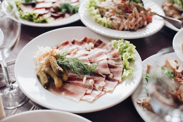 Różnorodność smacznych zimnych przekąsek podawanych na białych ceramicznych talerzach na weselnym stole okolicznościowym. asortyment gotowanych przekąsek i żywności na stole w restauracji. obchody bożego narodzenia lub nowego roku.