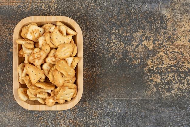 Różnorodność solonych krakersów w drewnianej misce.