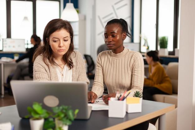 Różnorodność startupów, praca zespołowa, burza mózgów siedząc przy biurku w nowoczesnym biurze, planowanie strategii biznesowej w laptopie, wyszukiwanie rozwiązań do zarządzania