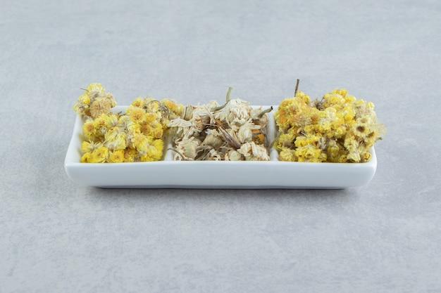 Różnorodność suchych kwiatów na białym talerzu.